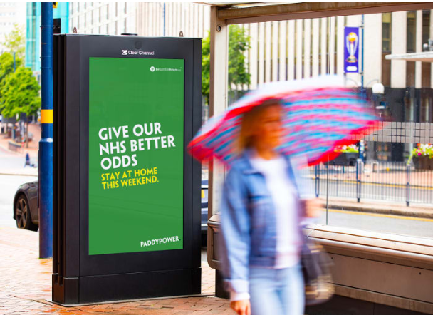 Outdoors poster on a bus shelter for Paddy Power - Give our NHS Better Odds. Stay at home this weekend.